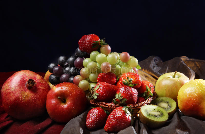 Juicy bright fruit, sprinkled with water, still life of seasonal fruits and berries, black background. stock photography