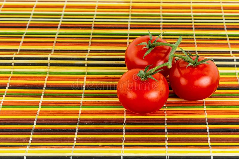 Juicy bright red tomatoes on a green branch three vegetables on a colorful bamboo base yellow orange green black royalty free stock image