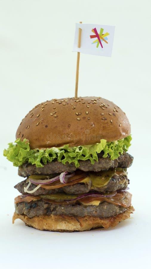 Juicy burger με το κρέας και φρέσκα λαχανικά σε ένα άσπρο υπόβαθρο, που μαγειρεύεται με τα χέρια σας στοκ φωτογραφία με δικαίωμα ελεύθερης χρήσης