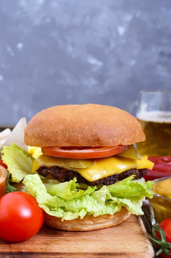 Juicy burger, τηγανιτές πατάτες, σάλτσες, μπύρα σε ένα ξύλινο υπόβαθρο Γρήγορο φαγητό στοκ εικόνες