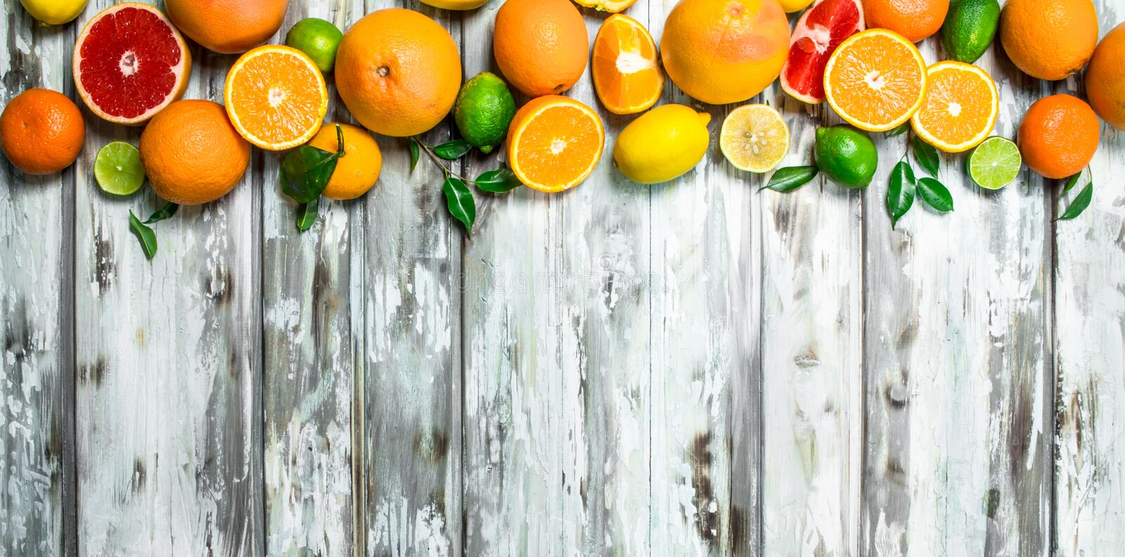 Juicy citrus with leaves. On wooden background stock images