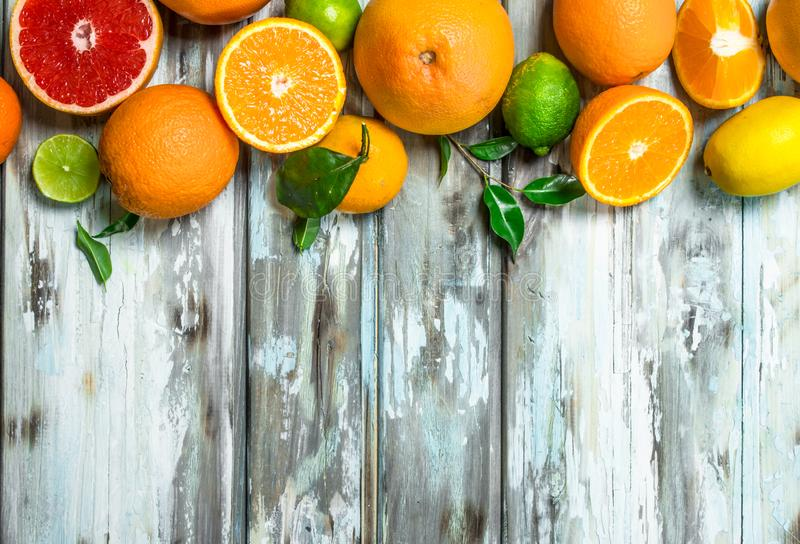 Juicy citrus with leaves. On wooden background royalty free stock photo