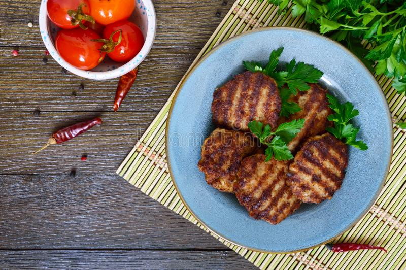 Juicy cutlets, fried on a grill in a ceramic plate and canned tomatoes. On a wooden background. Top view royalty free stock photos