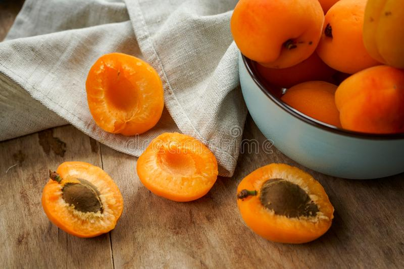 Juicy delicious apricot in a deep plate with a tablecloth. Selective focus, halves of apricots with seeds from whole fruits on a dark textured wooden Board, into stock images