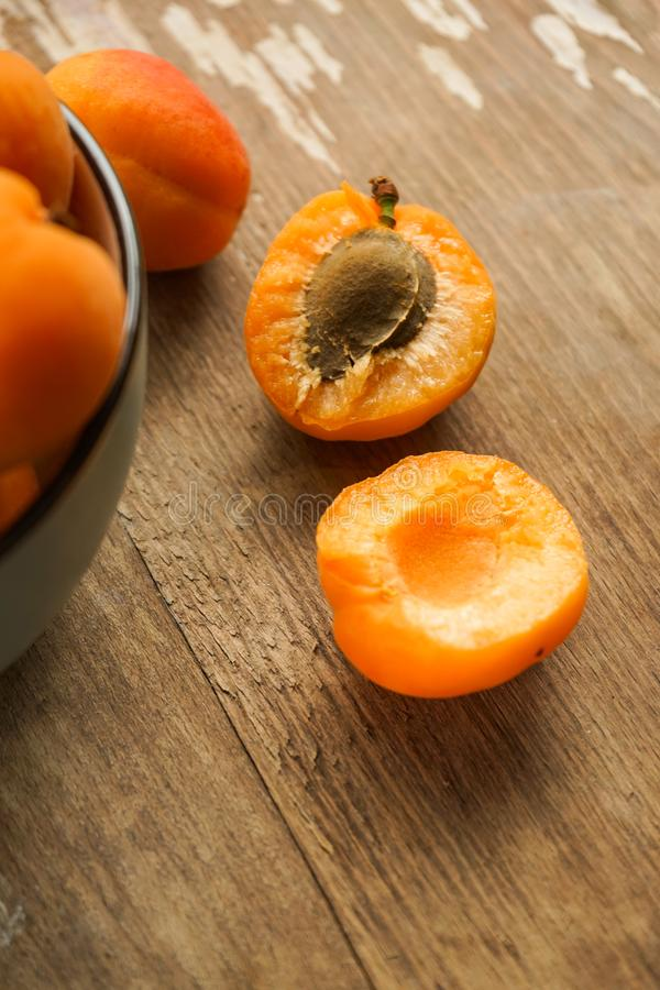 Juicy delicious apricot halves with bone and full ceramic more often whole PP. Selective focus, halves of apricots with seeds from whole fruits on a dark stock photo