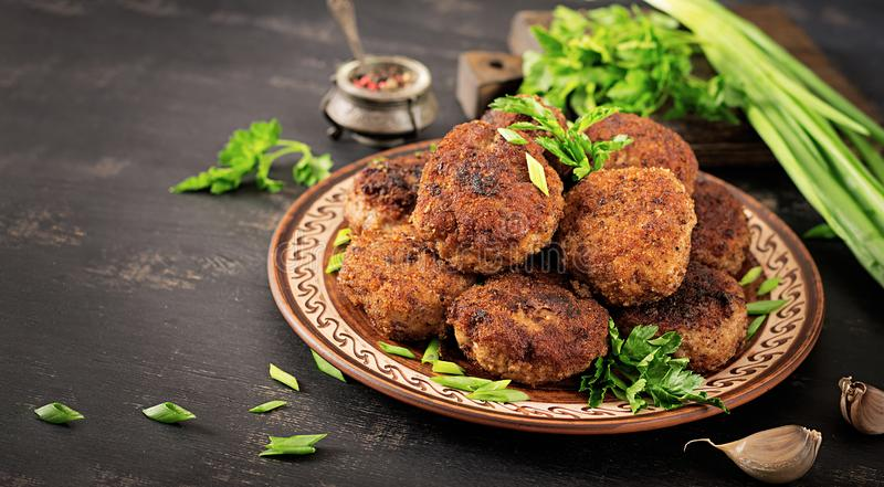 Juicy delicious meat cutlets on a dark table. Russian cuisine stock image