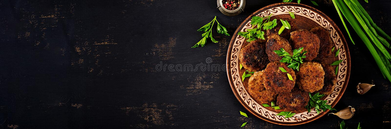Juicy delicious meat cutlets on a dark table. Russian cuisine. Banner.  Top view stock image