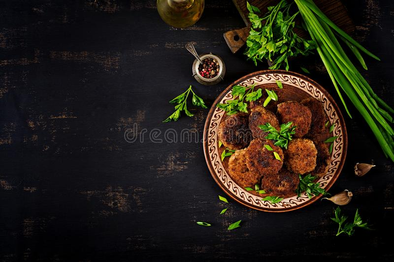Juicy delicious meat cutlets on a dark table. Russian cuisine. Top view stock photos
