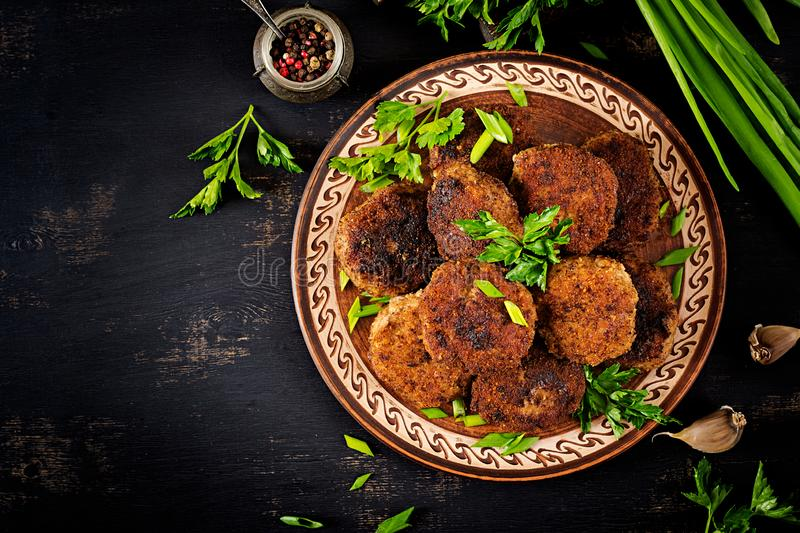 Juicy delicious meat cutlets on a dark table. Russian cuisine. Top view royalty free stock photo