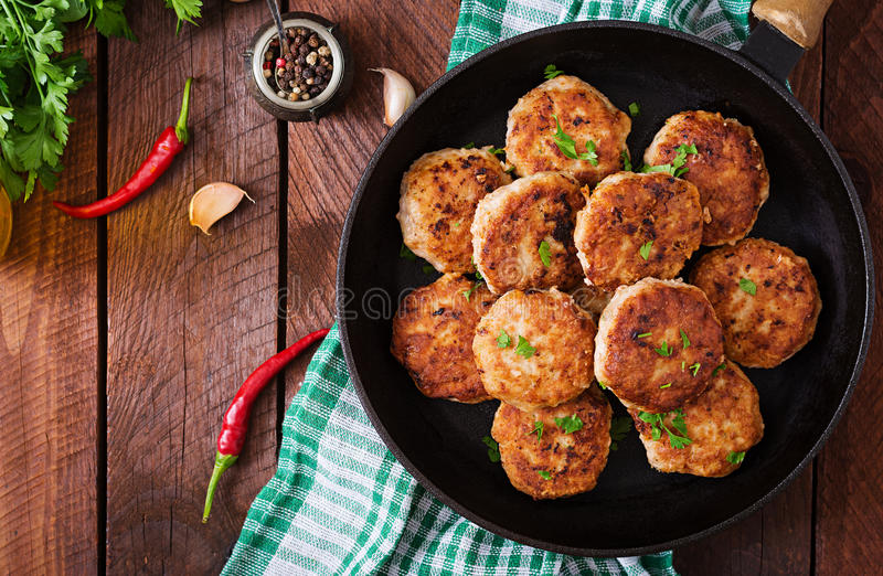 Juicy delicious meat cutlets in pan. On a wooden table. Top view royalty free stock images