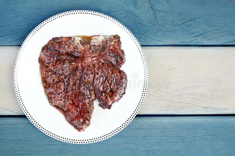 Juicy Delicious thick grilled T-bone beef steak viewed from above. Flag of Argentina background stock photo