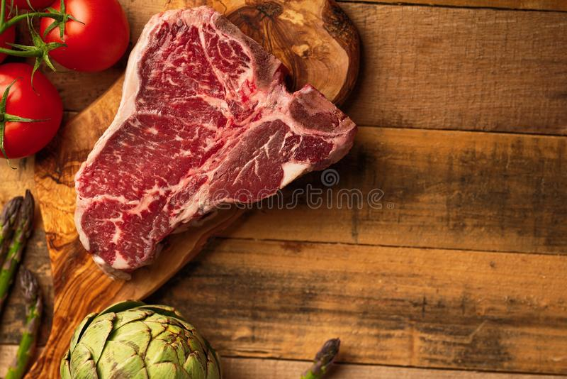 Juicy fresh piece of marbled beef steak with vegetables for grilling. Culinary background, recipe book, delicious food, Steak. Cooking. With space, horizontal stock photo