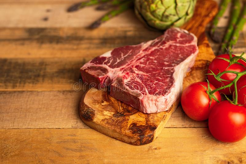 Juicy fresh piece of marbled beef steak with vegetables for grilling. Culinary background, recipe book, delicious food, Steak. Cooking. With space, horizontal stock image
