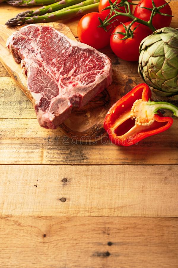 Juicy fresh piece of marbled beef steak with vegetables for grilling. Culinary background, recipe book, taste food, Steak cooking. With space, vertical photo royalty free stock photography