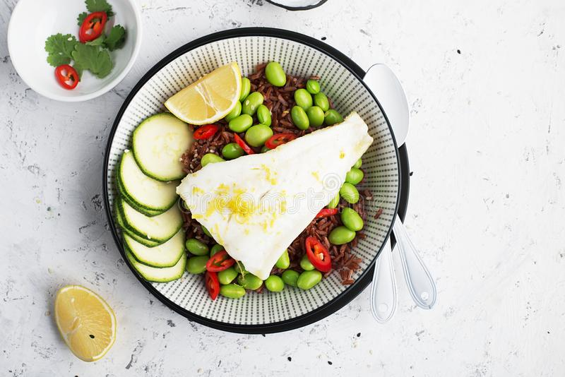 Juicy fresh steam white sea fish fillets on a cushion of red fragrant rice and fresh vegetables: soybeans, capsicum royalty free stock photo