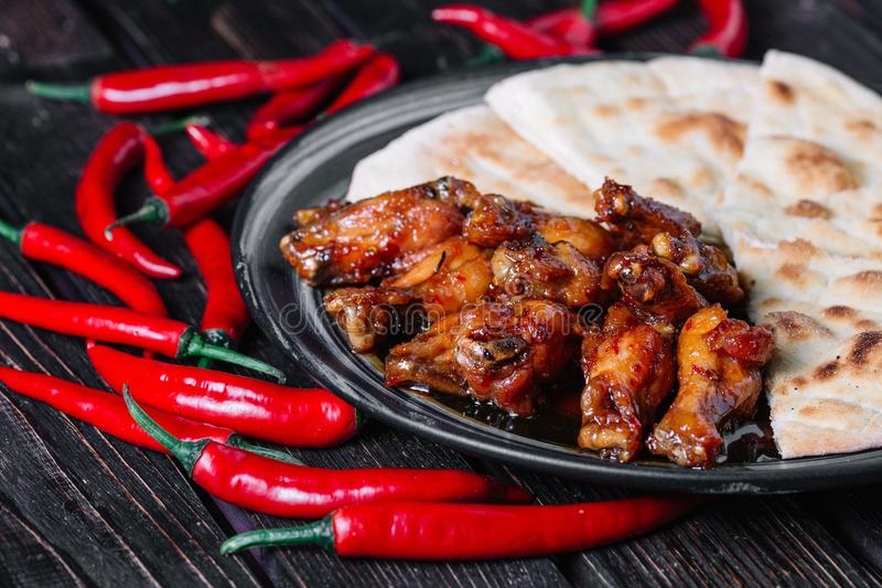 Juicy fried chicken wings with flatbread and chilli peppers stock photography