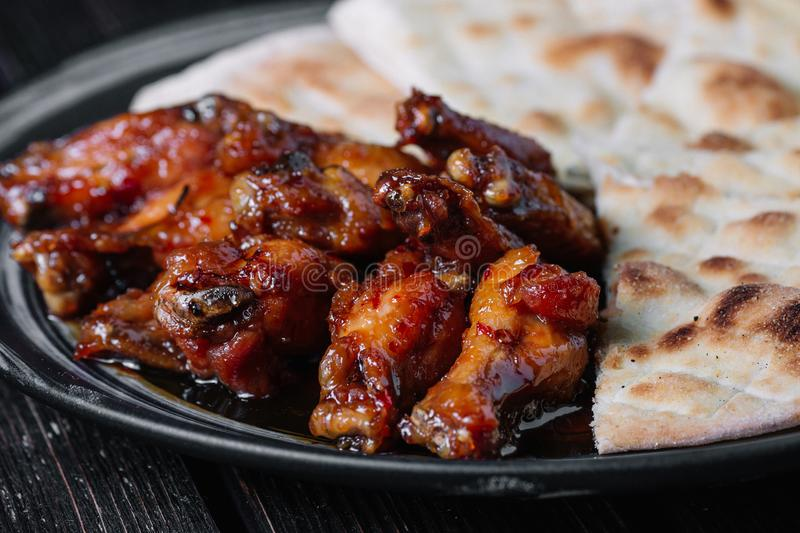Juicy fried chicken wings with flatbread on wood backiground royalty free stock photo