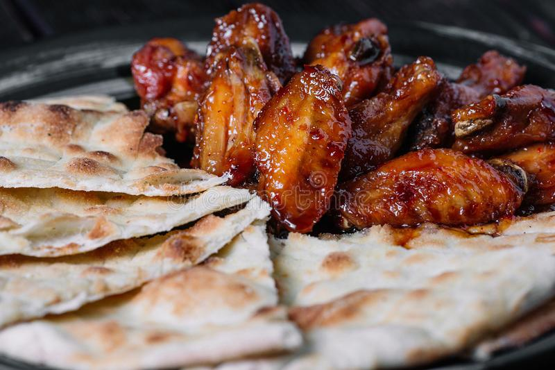 Juicy fried chicken wings with flatbread on wood backiground royalty free stock images
