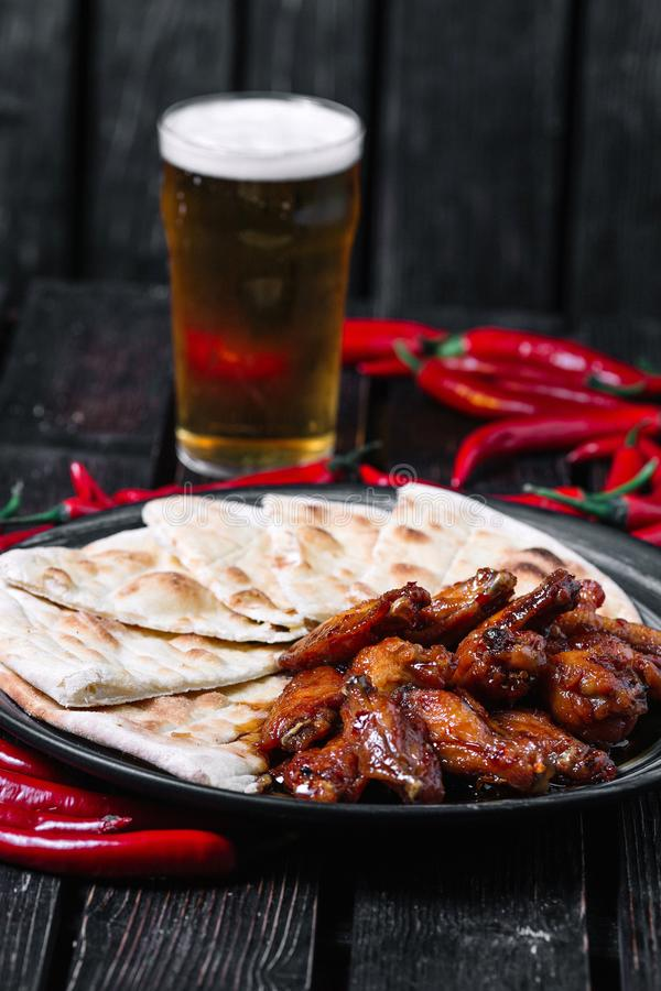 Juicy fried chicken wings glass of beer and chilli peppers on wood backiground royalty free stock image