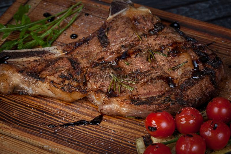 Juicy, fried, tender steak with vegetables and sauces on a special stand stock photo