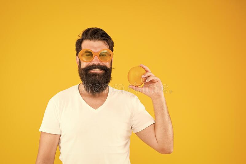 Juicy fruit. Man bearded hipster in orange sunglasses on yellow background. Cheerful guy with ripe fruit. Summer royalty free stock images