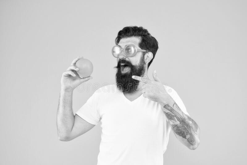 Juicy fruit. Summer nutrition. Hipster with beard in summer mood. Man bearded hipster in orange sunglasses on yellow royalty free stock images