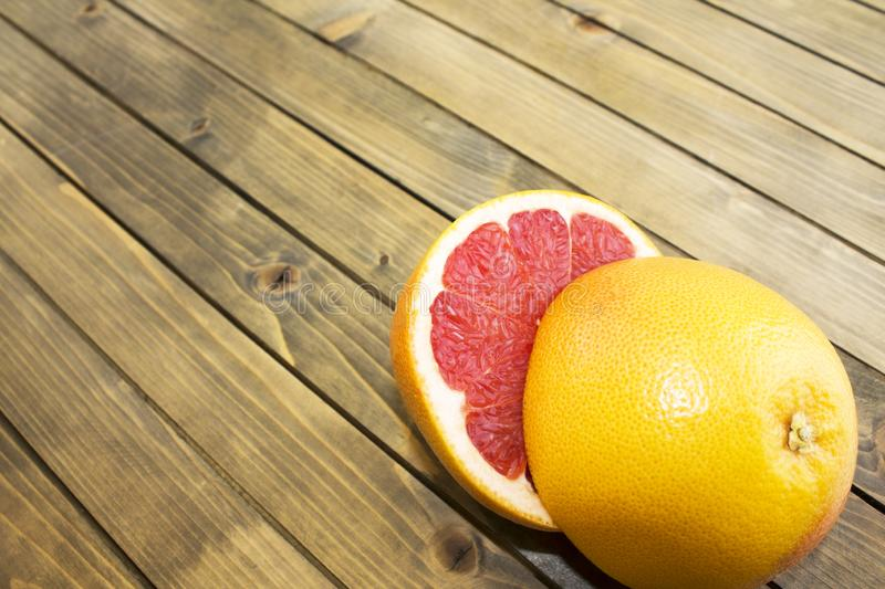 Juicy red grapefruits on old wooden background stock photos