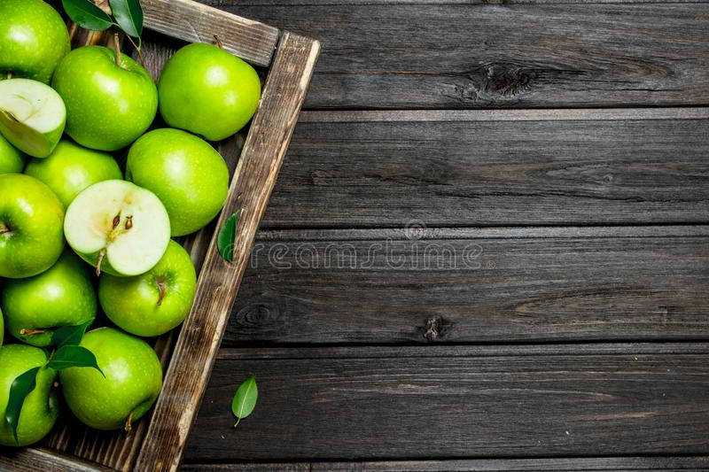 Juicy green apples and Apple slices in a wooden box. On a dark wooden background royalty free stock photography