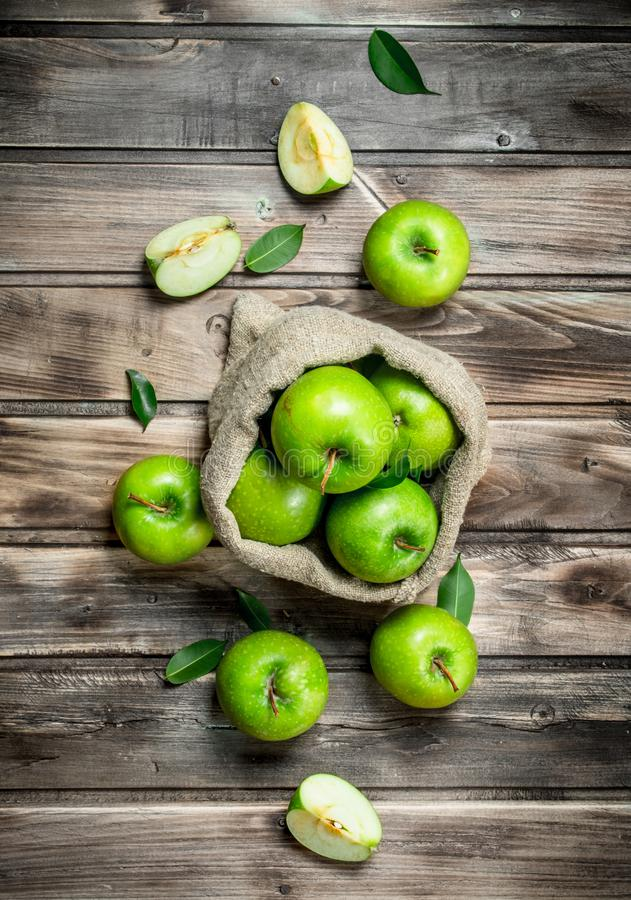 Juicy green apples in an old bag. On grey wooden background stock image