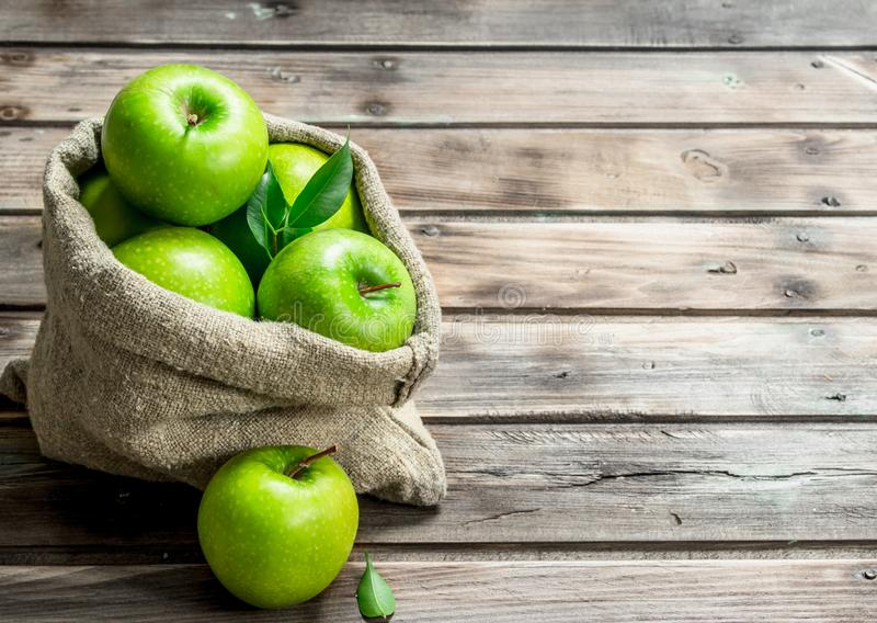 Juicy green apples in an old bag. On grey wooden background royalty free stock photos