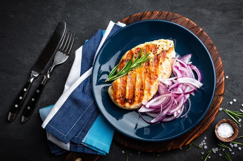 Juicy grilled chicken meat, fillet with fresh marinated onion on plate. Black background, top view, closeup royalty free stock photography