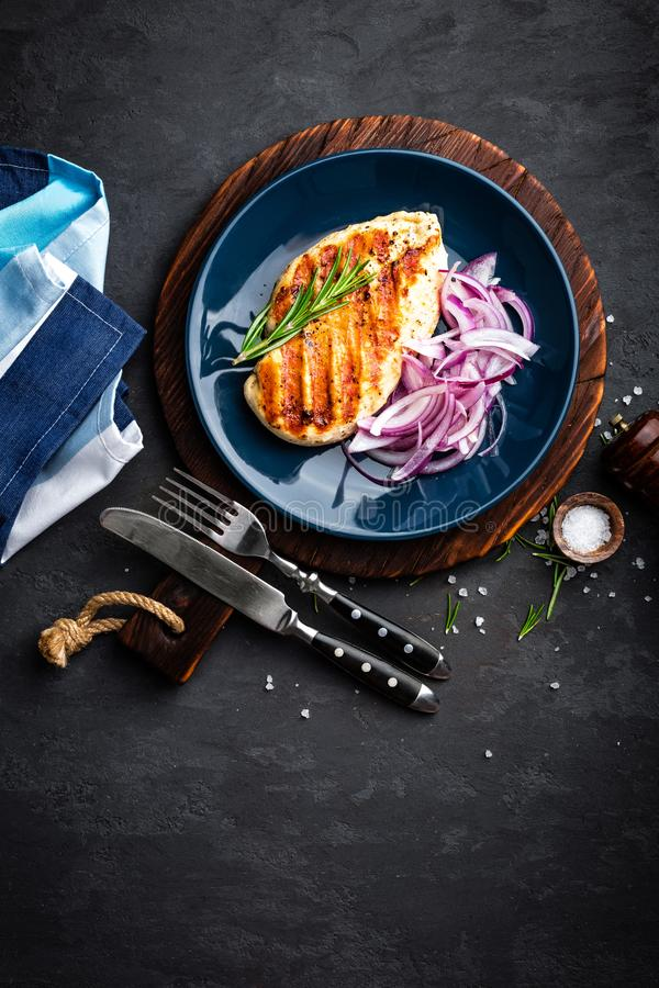 Juicy grilled chicken meat, fillet with fresh marinated onion on plate. Black background, top view, closeup stock image