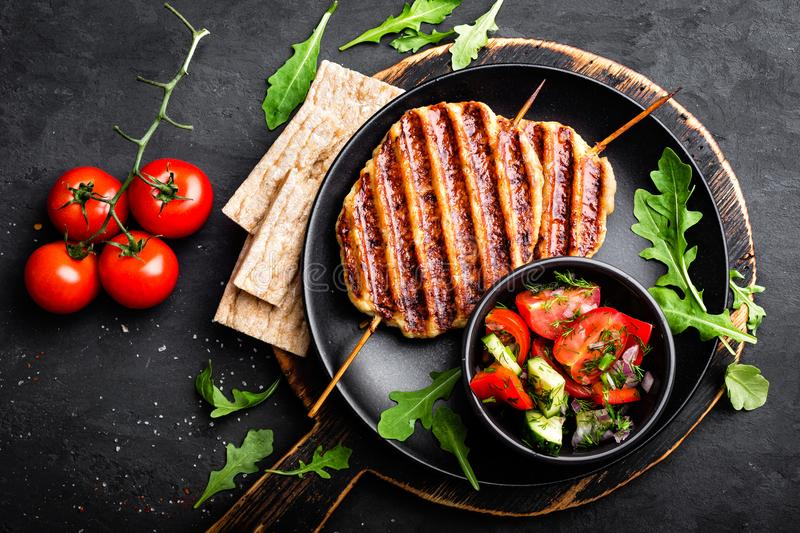 Juicy grilled chicken meat lula kebab on skewers with fresh vegetable salad on black background royalty free stock photos