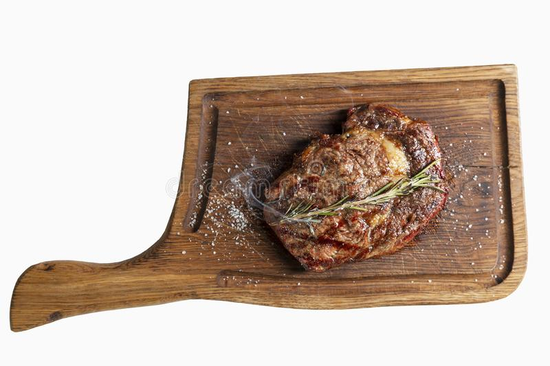 Juicy grilled meat steak with a branch of rosemary and with smoke on a wooden board. View from above. Isolated over white royalty free stock image