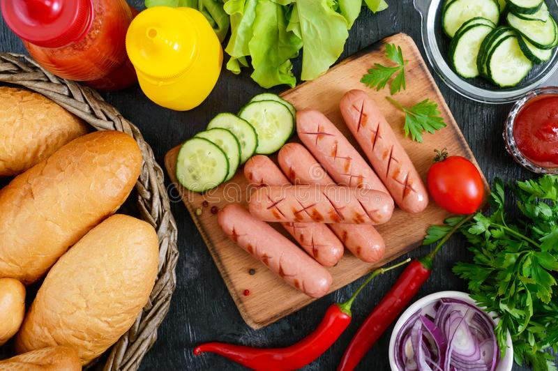 Juicy grilled sausages, sauces, fresh vegetables, crispy buns, on a wooden background royalty free stock image