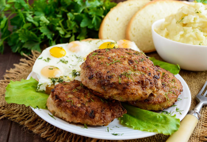 Juicy home cutlets fried eggs and mashed potatoes on a wooden background. royalty free stock images