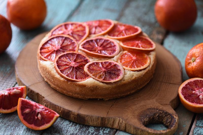 Juicy homemade cake with blood orange slices served with raw ora. Nges on oak cutting board over shabby rustic blue background closeup stock photo