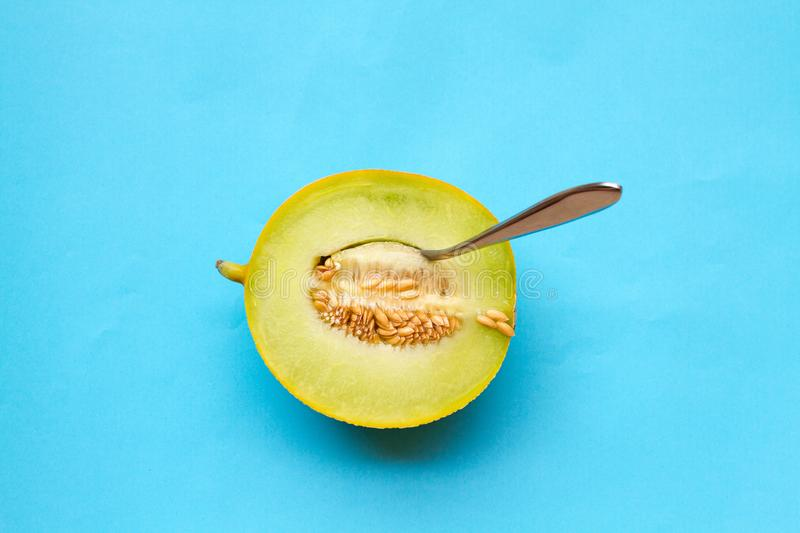 A juicy honeydew melon and a spoon. On a blue background royalty free stock images