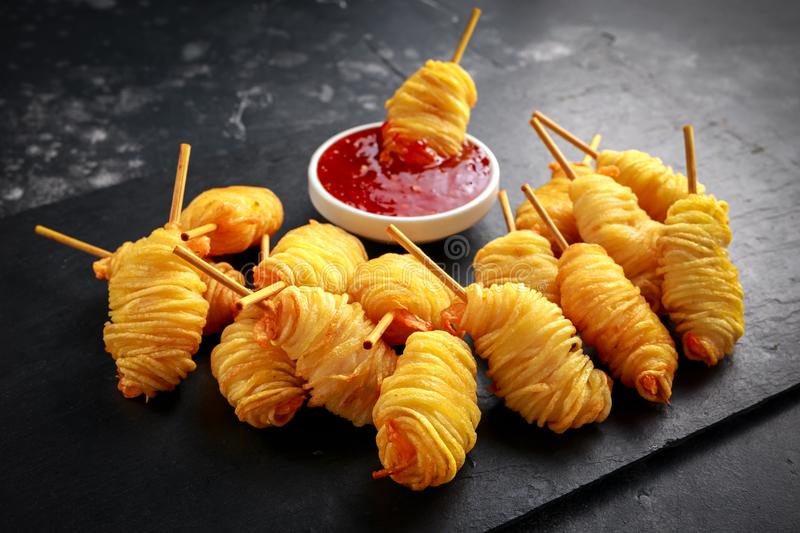 Juicy king prawns wrapped in little spirals of crisp, golden potato on skewers served with sweet chillie sauce. stock photos