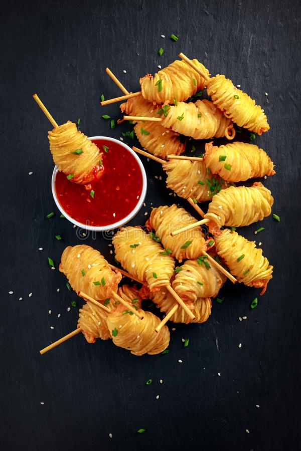 Juicy king prawns wrapped in little spirals of crisp, golden potato on skewers served with sweet chillie sauce. royalty free stock photo