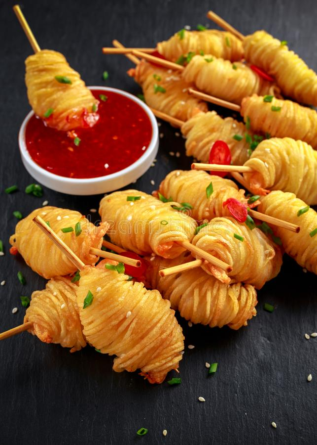 Juicy king prawns wrapped in little spirals of crisp, golden potato on skewers served with sweet chillie sauce. royalty free stock photos