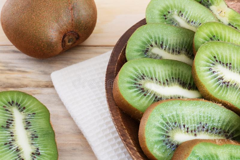 Juicy kiwi slices on a wooden plate on the table close-up, delicious fruit wood, dietary products, healthy ingredients, tropical f royalty free stock photography