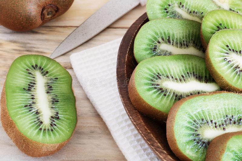 Juicy kiwi slices on a wooden plate on the table close-up, delicious fruit wood, dietary products, healthy ingredients, tropical f stock photo
