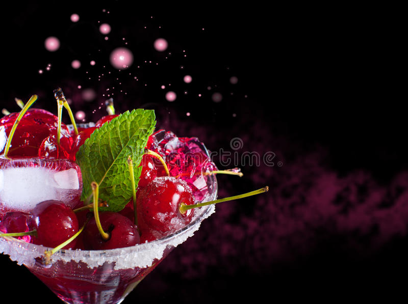 Juicy maraschino cherry on a black background. royalty free stock photography