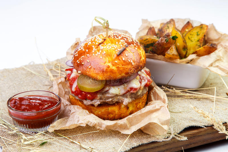Juicy meat burger with garnish and sauce on wooden board on whit royalty free stock photography