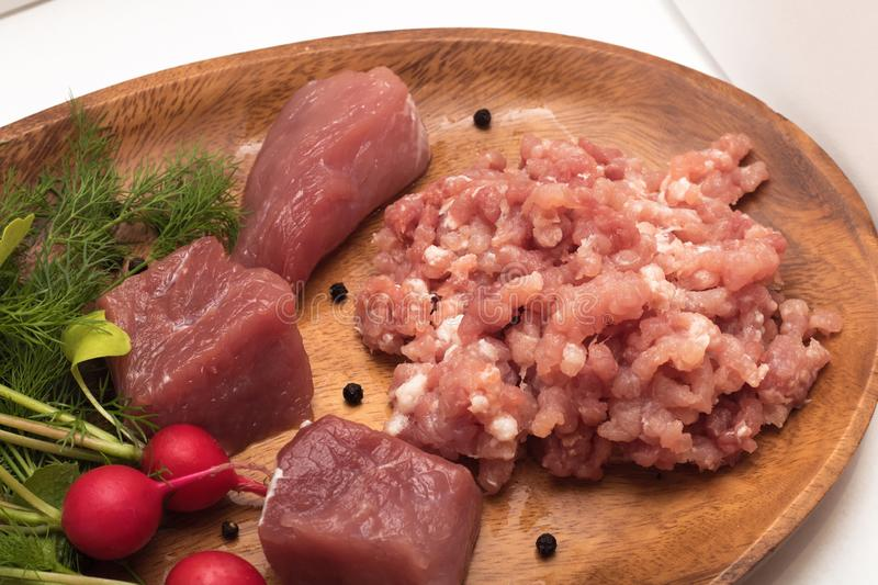 Juicy meat chopped in minced close-up served with large pieces of raw meat fresh vegetables, seasoning and herbs royalty free stock photos