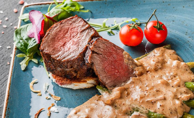 Juicy medium beef fillet steaks mignon with asparagus and mushroom sauce on on dark stone background. Hot Meat Dishes. Top view. Juicy medium beef fillet steaks royalty free stock photos