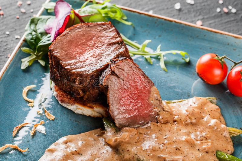 Juicy medium beef fillet steaks mignon with asparagus and mushroom sauce on on dark stone background. Hot Meat Dishes. Top view.  stock image