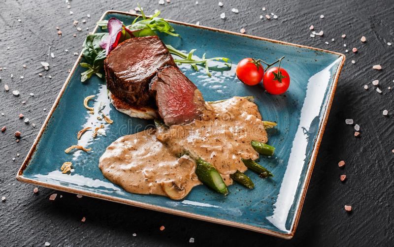 Juicy medium beef fillet steaks mignon with asparagus and mushroom sauce on on dark stone background. Hot Meat Dishes. Top view.  stock photography