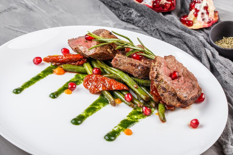 Juicy medium beef fillet steaks mignon with green beans, pomegranate and sauce in plate on grey background royalty free stock photography
